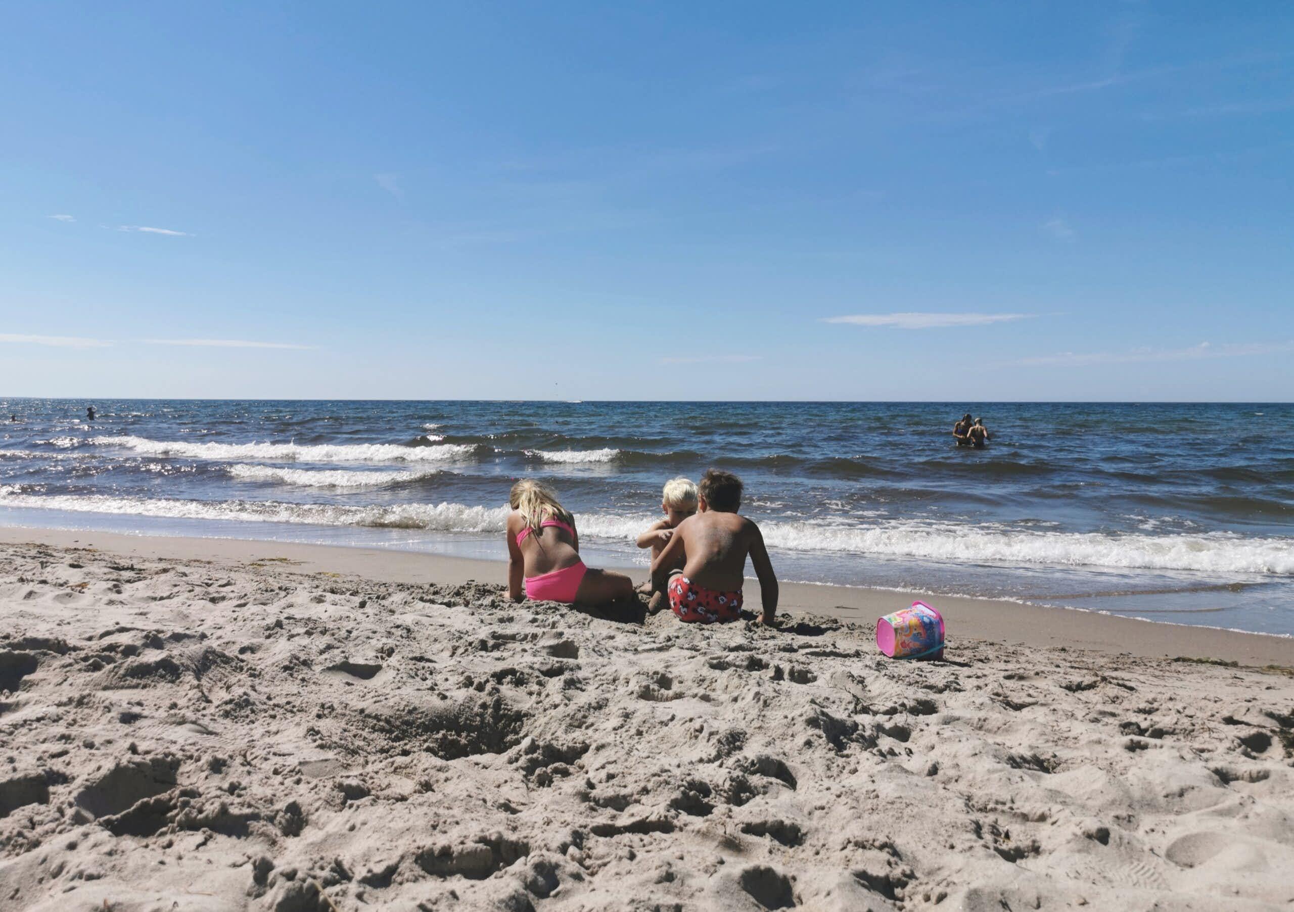 Tre barn leker på en sandstrand