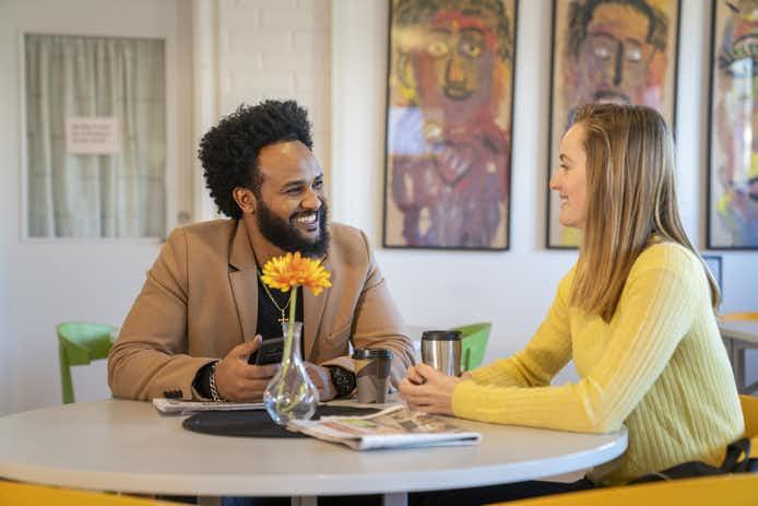 En man och en kvinna sitter vid ett bord i ett samtal på en arbetsplats.