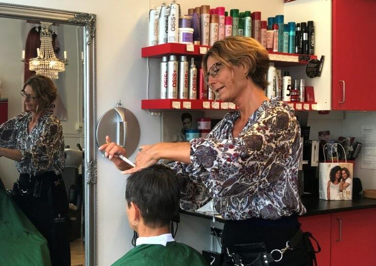 Frisör klipper hår på person