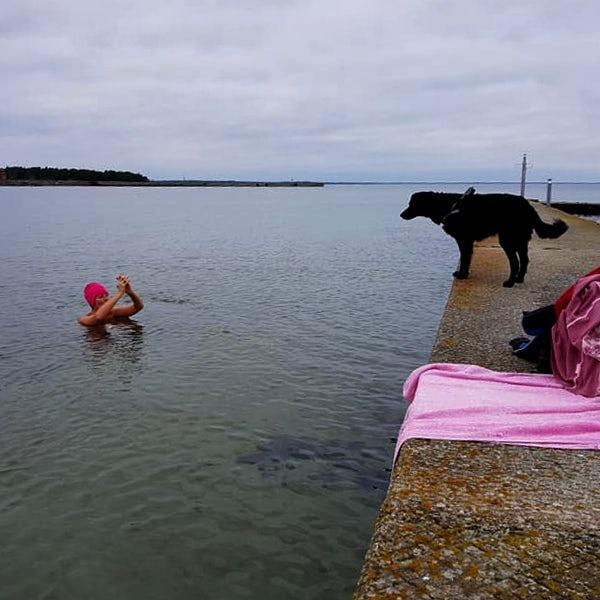 Kvinna badar och hund tittar på.