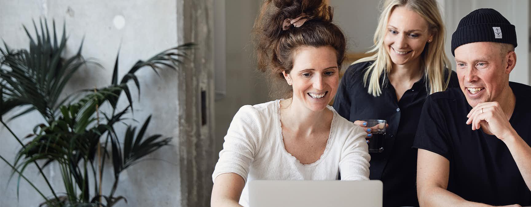 Två kvinnor och en man jobbar framför en dator.