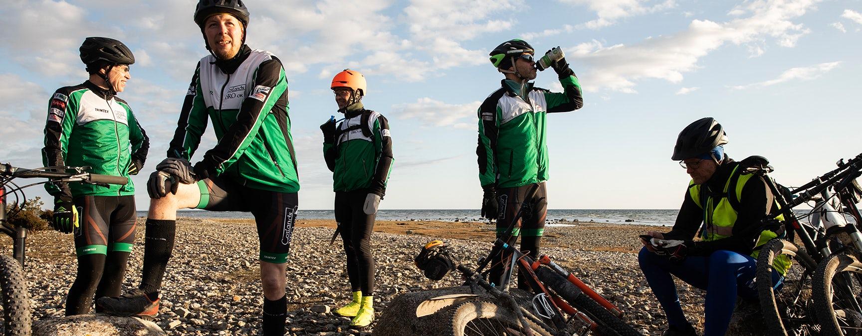 Fem manliga cyklister tar en paus i solnedgången på Ekstakusten.