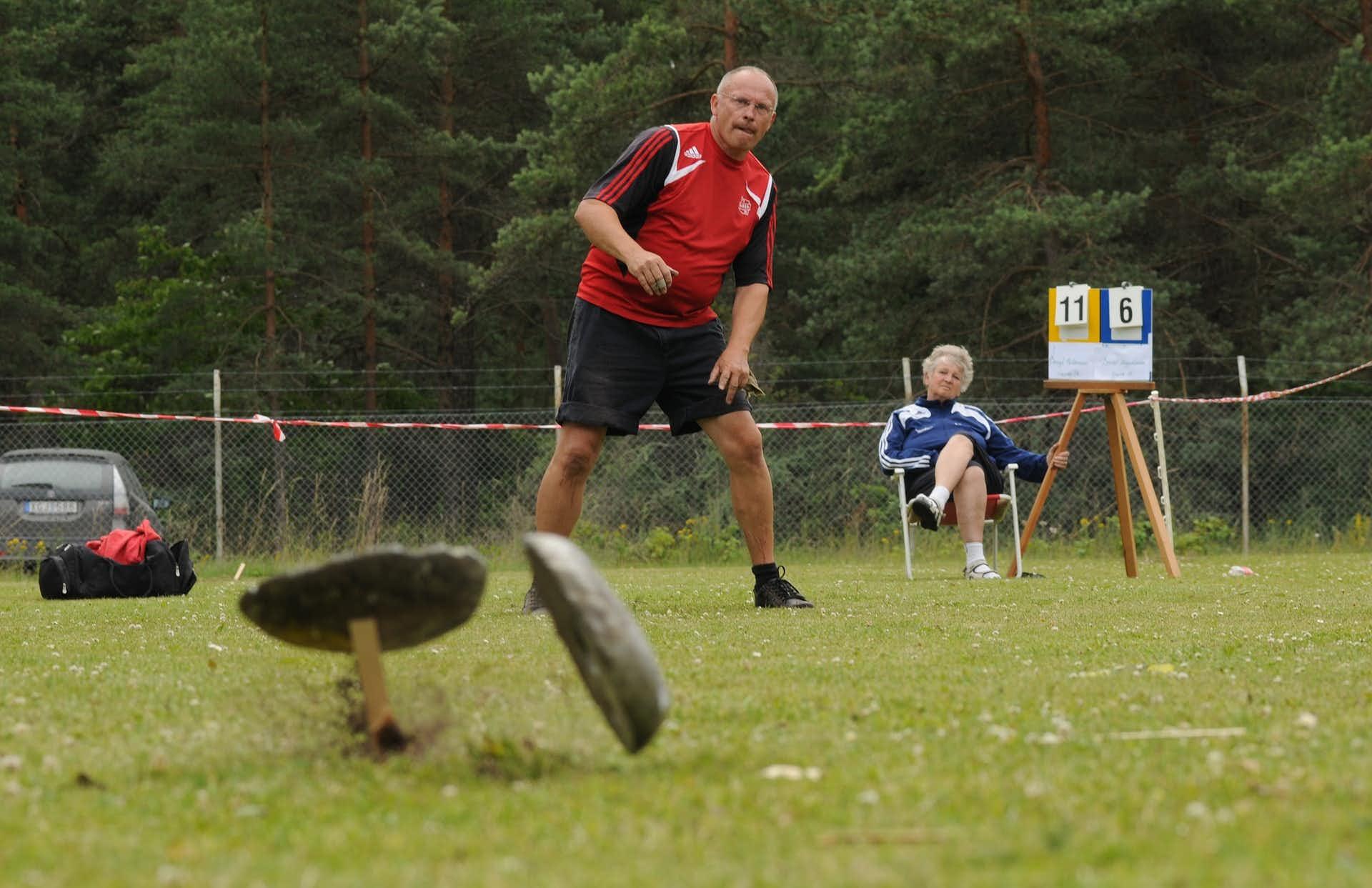 Man kastar varpa på Stångaspelen på Gotland. Kvinna i bakgrunden håller ordning på poängställningen i matchen. Det är sommar.