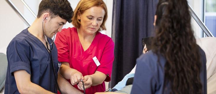 Elever på en undersköterkseutbildning får instruktioner av en lärare.